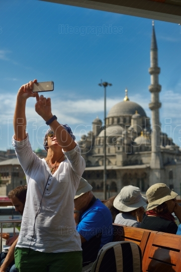 Female tourist taking selfie photo on a cruise boat in Istanbul