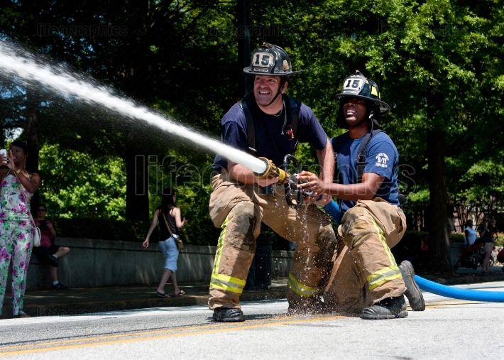 Firemen aim hose at target in atlanta muster competition