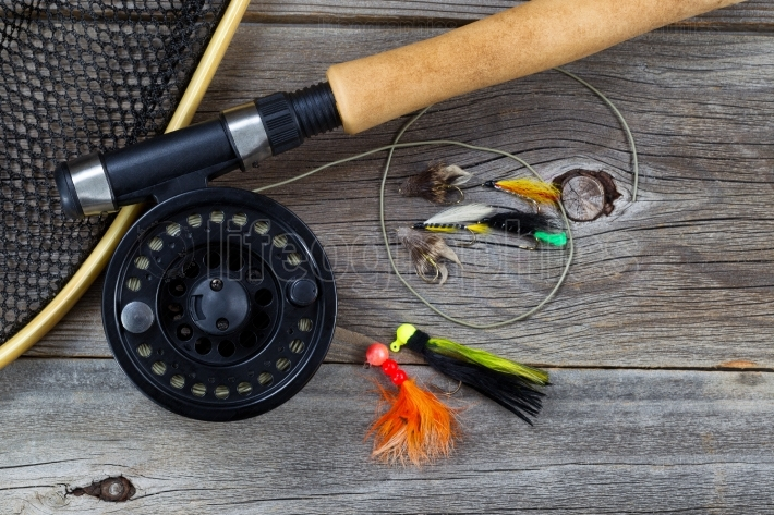 Fishing Fly reel with accessories on wood