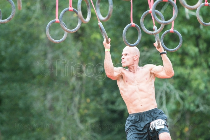 Fit male grasps rings in extreme obstacle course race