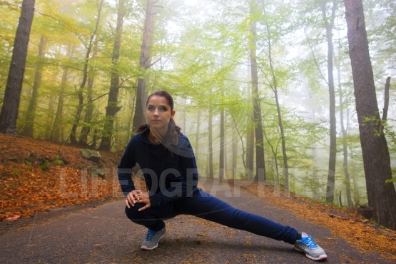 Fit woman stretching her legs against peaceful autumn scene in f