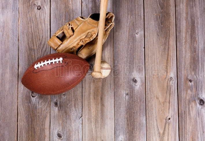 Football and baseball equipment on rustic wooden boards