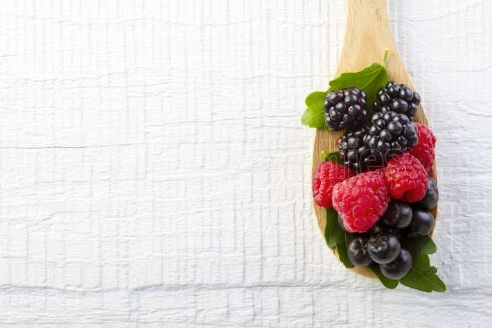 Forest berries in wooden spoon on white wood