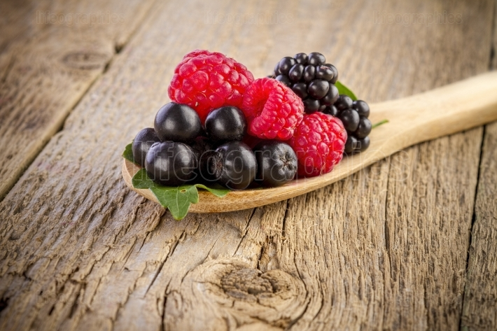 Forest berries in wooden spoon on wood