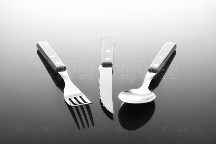 Fork knife and spoon on glossy table surface