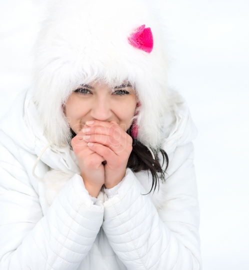 Freezing young woman warming her hands