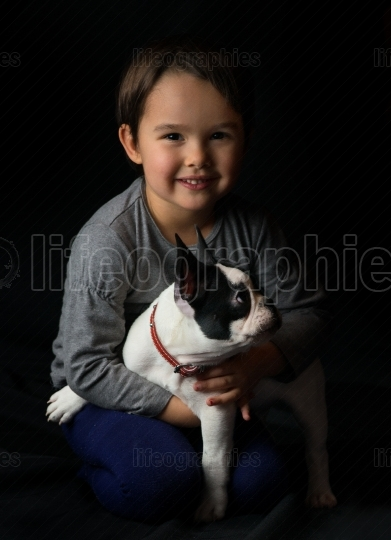 French bulldog and little girl playing isolated on black background