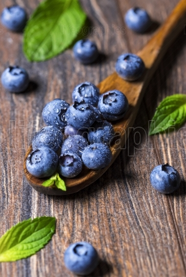 Fresh blueberries and mint leaf on wooden spoon