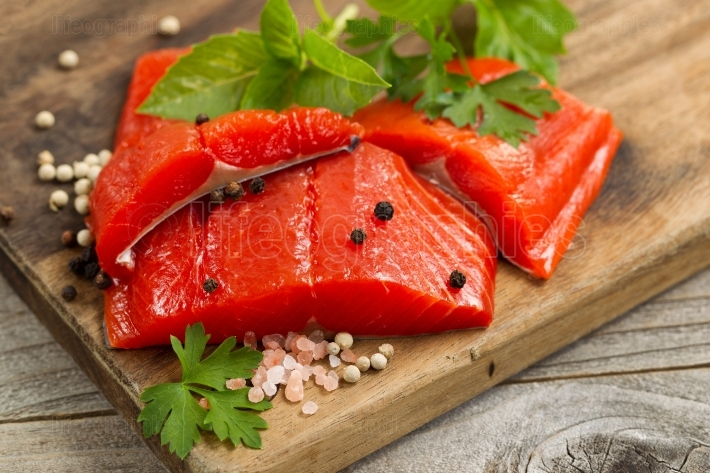 Fresh bright red Copper River Salmon fillets on rustic wooden se