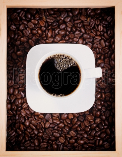 Fresh cup of dark coffee in box with roasted beans