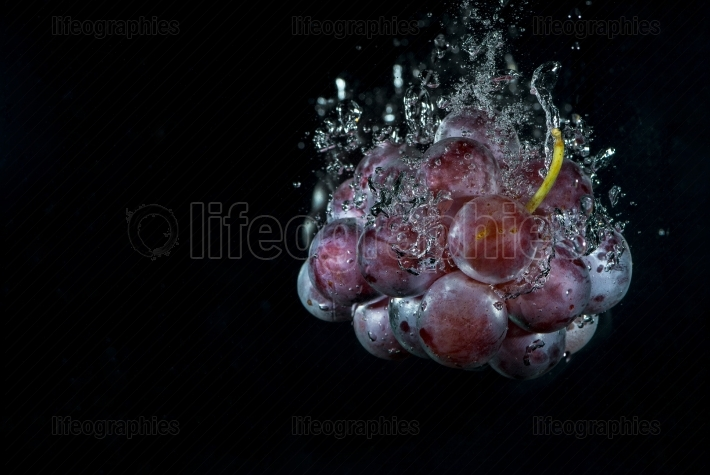 Fresh grape in water with air bubbles