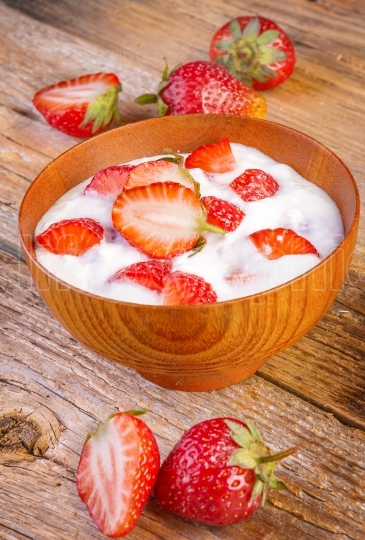 Fresh organic greek yogurt with strawberries on wooden