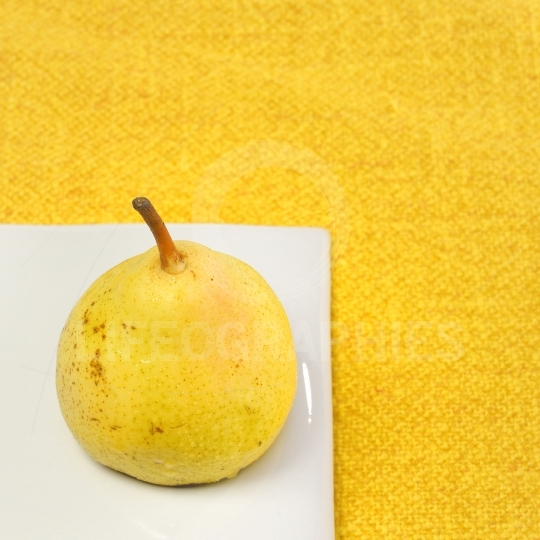 Fresh pear isolated on yellow background