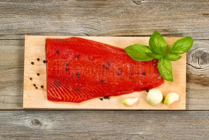 Fresh red salmon fillet on cedar cooking plank with spices and h