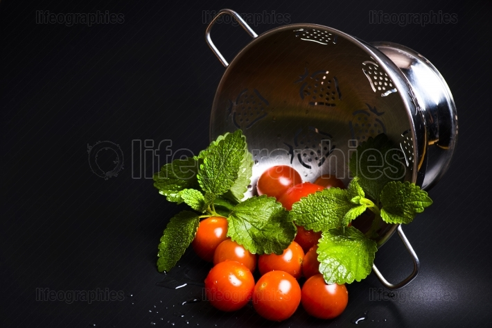 Fresh tomatoes and lemon balm in a metal strainer