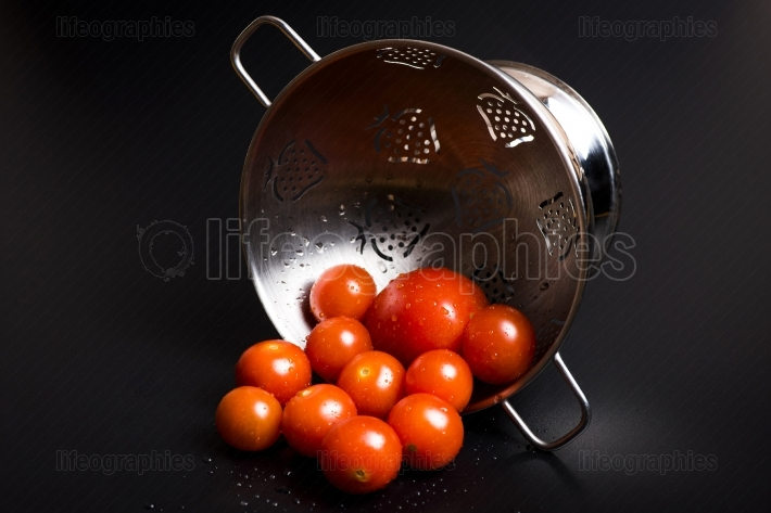 Fresh tomatoes in a metal strainer