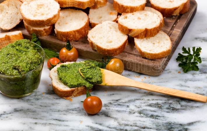 Freshly made pesto and sliced bread on server