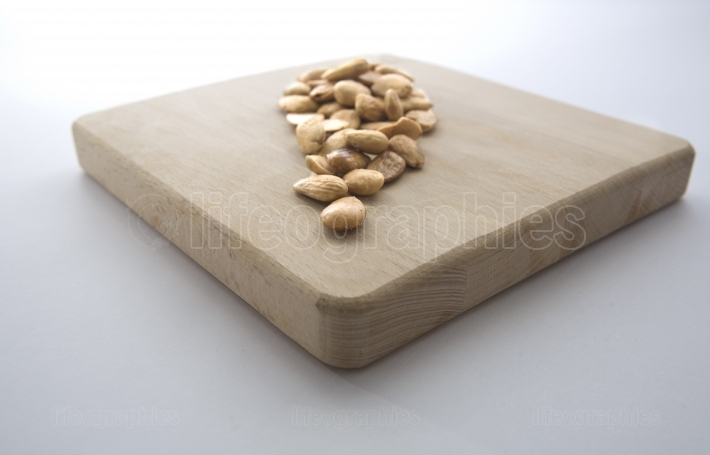 Fried almonds over wooden board