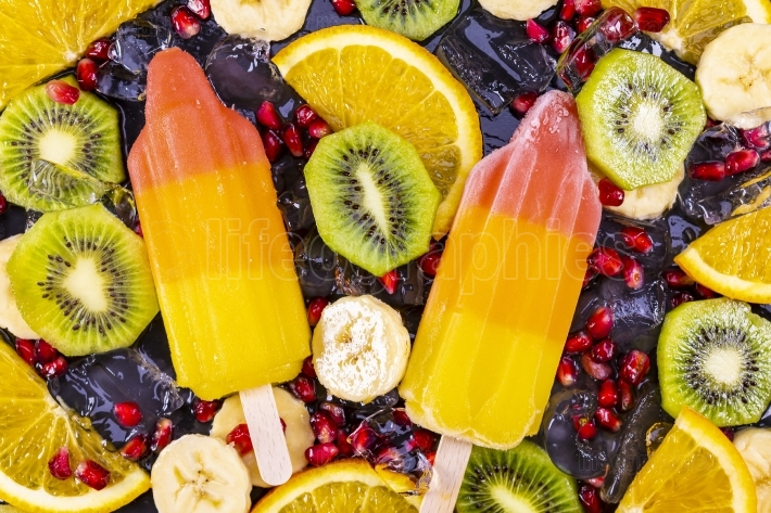 Fruit ice cream on stick with slices fruits on black