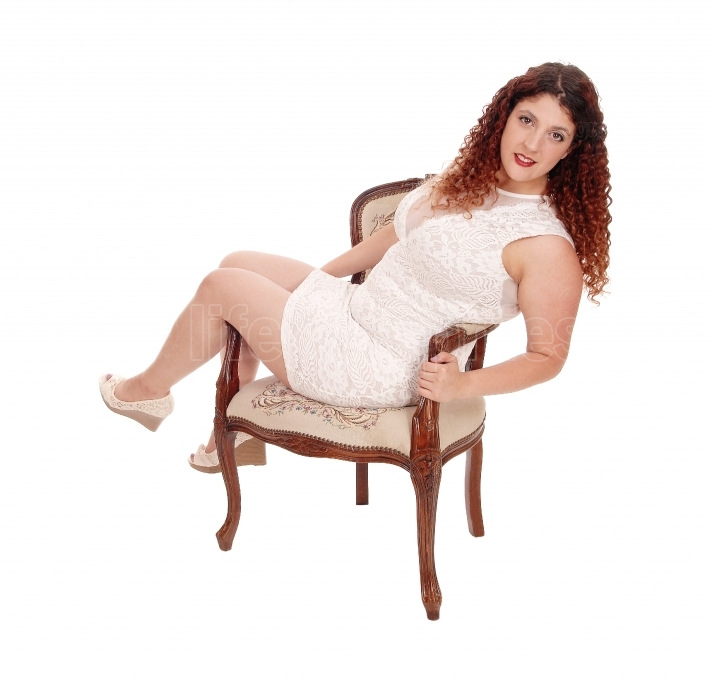 Full figured woman sitting in armchair