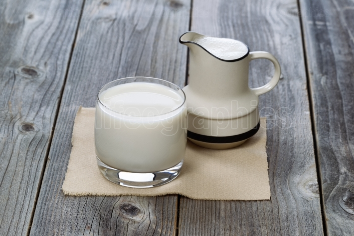 Full Glass of fresh milk and pourer on old wood