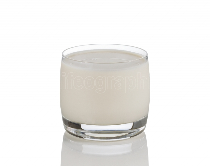 Full glass of fresh milk on white with reflection