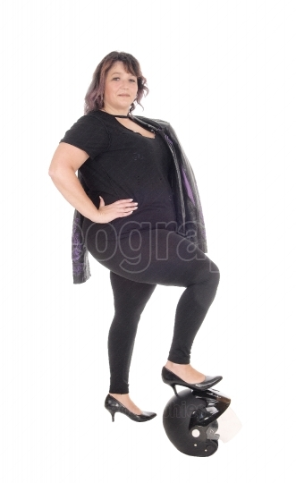 Full size woman standing with leg on helmet