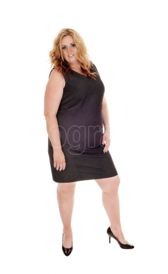Full sized woman standing in black dress