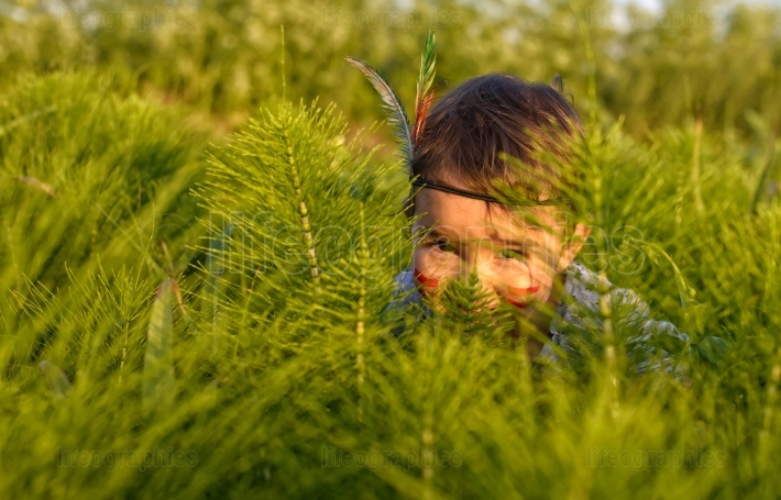 Funny little girl as indian  hiding behind grass