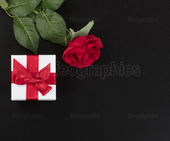 Gift box and a single red rose on dark stone background