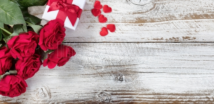 Gift box with red roses and hearts on rustic wood