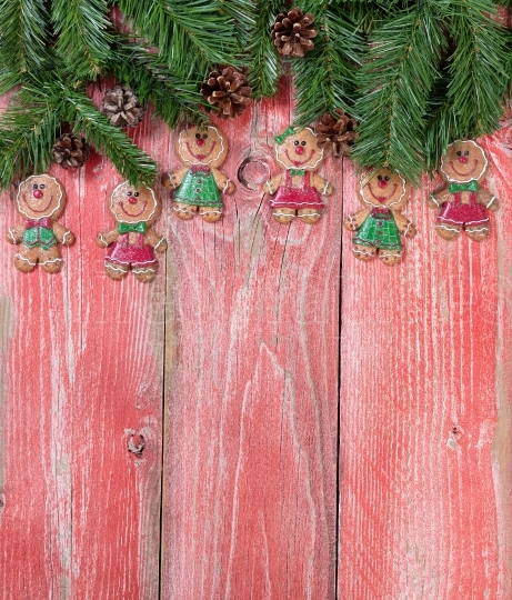 Gingerbread cookies and evergreen branches on rustic red wooden