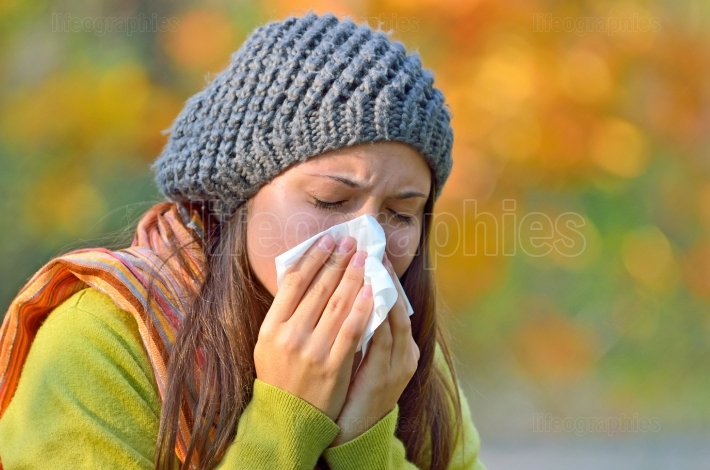 Girl  sneezing in tissue.