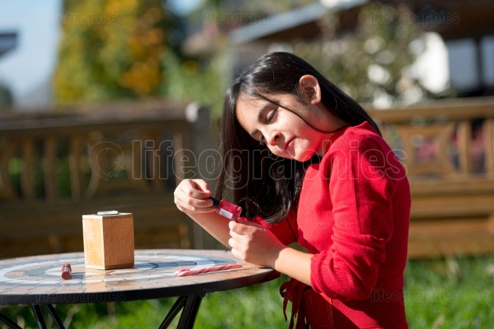 Girl dressed in red sitting in garden