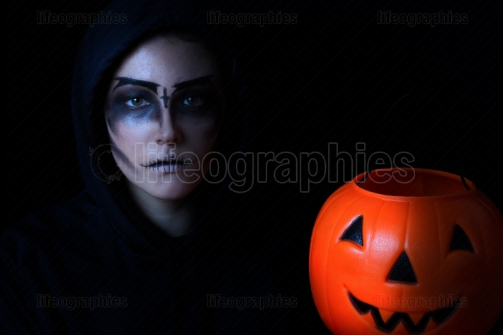 Girl dressed in scary face paint with pumpkin bucket on black ba