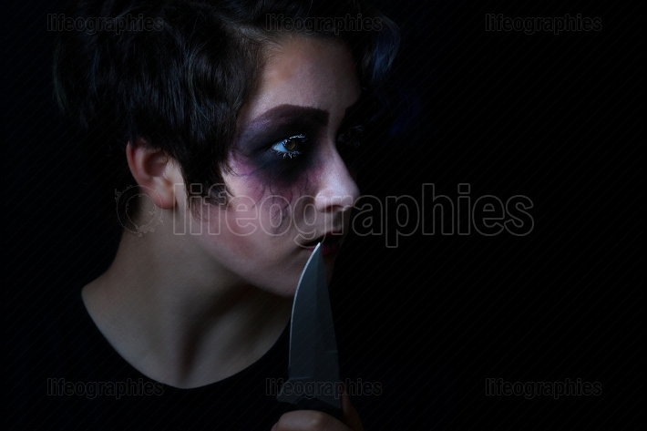 Girl in scary makeup with combat knife on black background