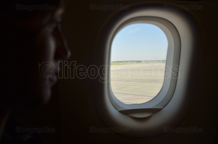 Girl looking through the window of the airplane