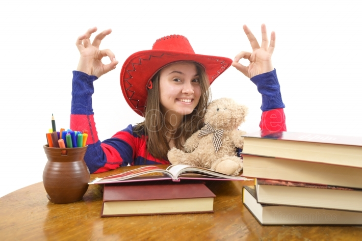 Girl making ok sign sitting on the table with stack of books, isolated on white
