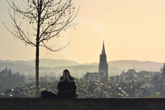 Girl silhouette on sunset over old town of Bern