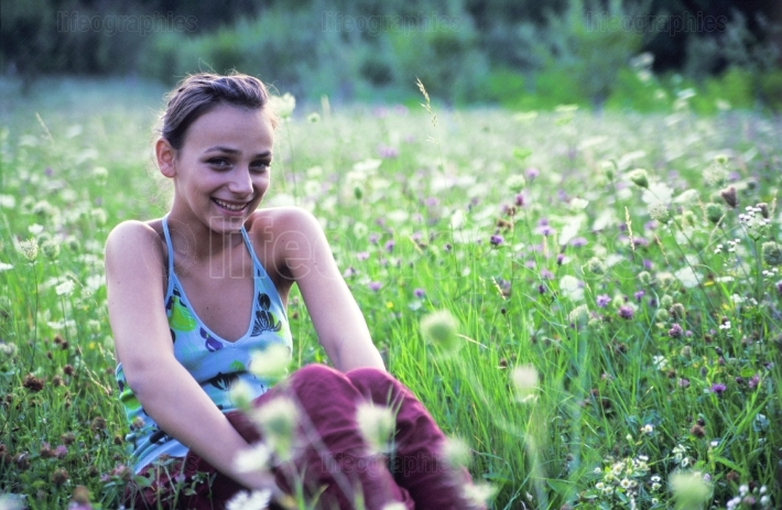Girl sitting in grass smiling