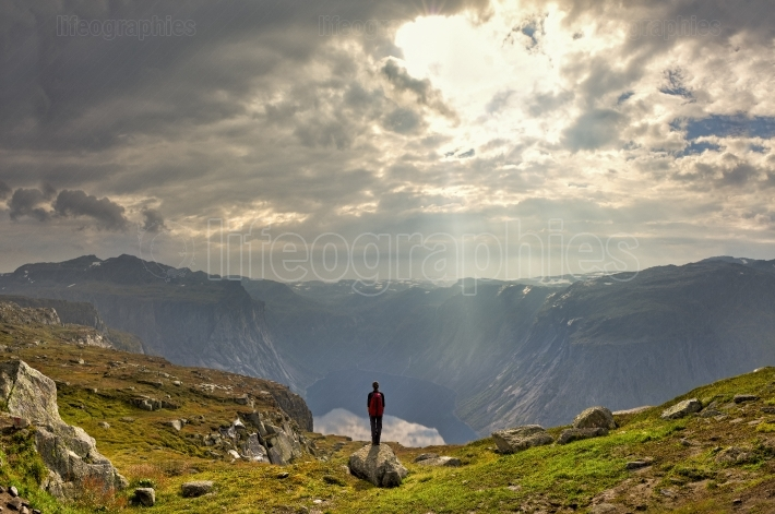 Girl sitting on the edge of the fjord close to Trolltunga stone.