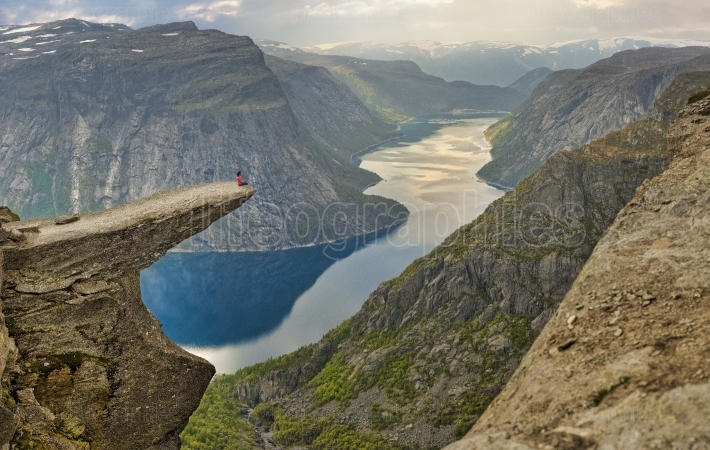 Girl sitting on Trolltunga stone.
