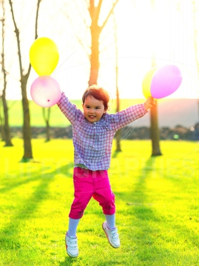 Girl with balloons jumping outdoor, at sunset