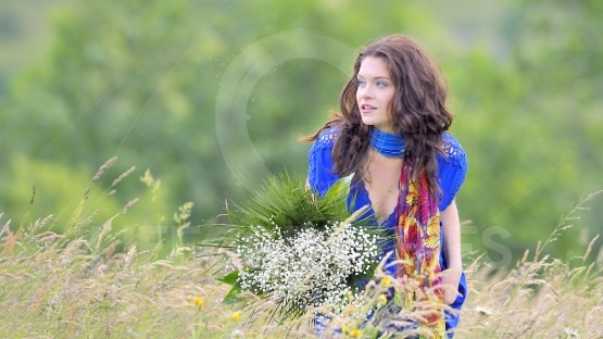 Girl with bouquet  in field