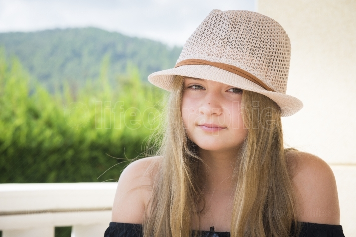 Girl with hat posing on a terrace