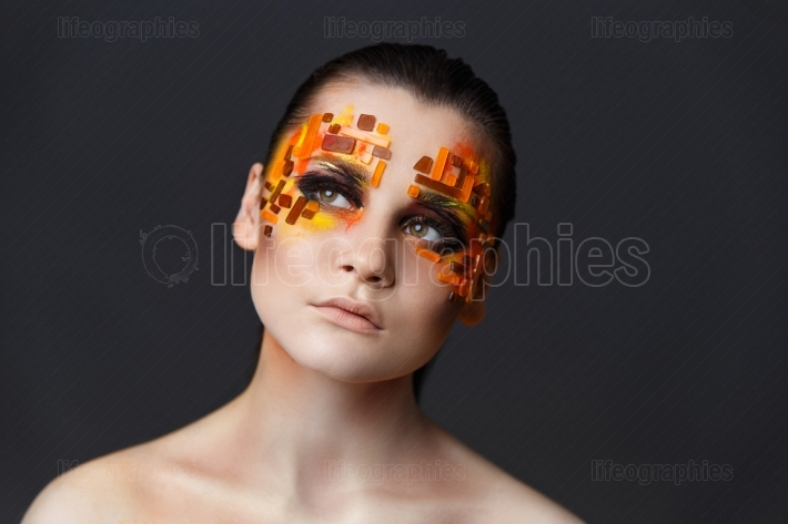 Girl with orange and red rhinestones on her face