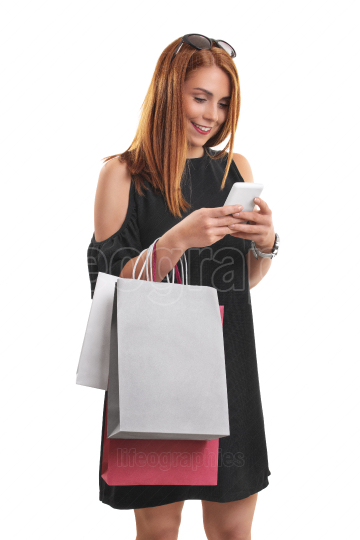Girl with shopping bags typing on her phone
