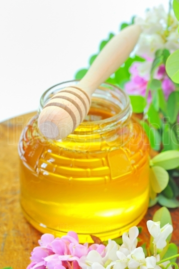 Glass jar full of honey and stick with acacia pink and white  fl