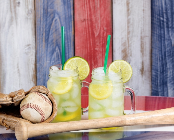 Glass jars filled with cold lemonade along with baseball sportin