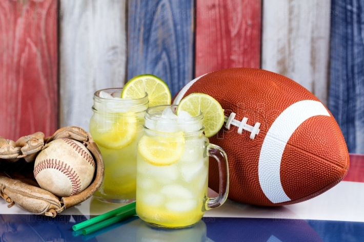 Glass jars filled with cold lemonade along with sporting objects